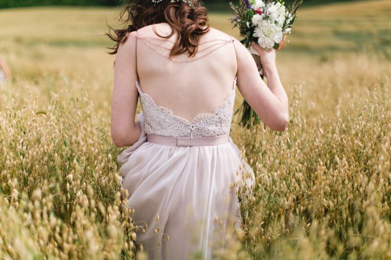 Back detail on Jess's gown as she walks through a golden field.