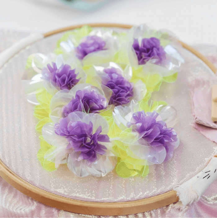 Clusters of purple, white and yellow sequin flowers on hoop